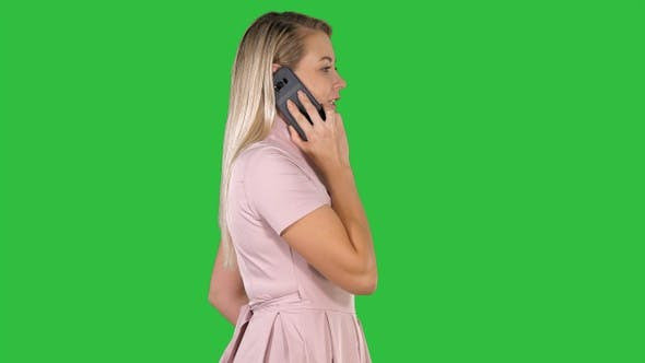 Young lady having call on a Green Screen, Chroma Key.