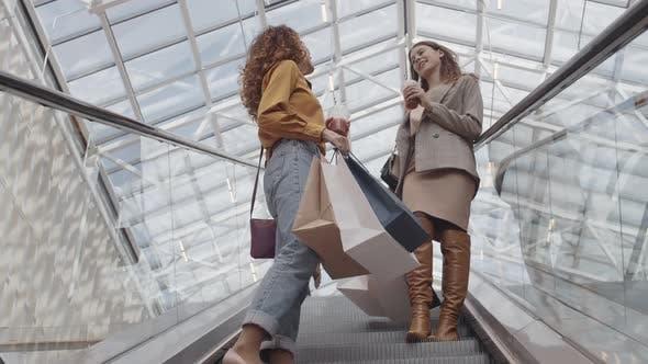 Attractive Women Going down on Escalator in Shop