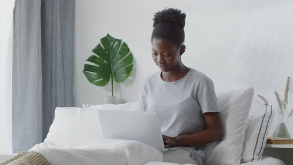 Thumbnail for Young Woman Sitting on Bed and Working