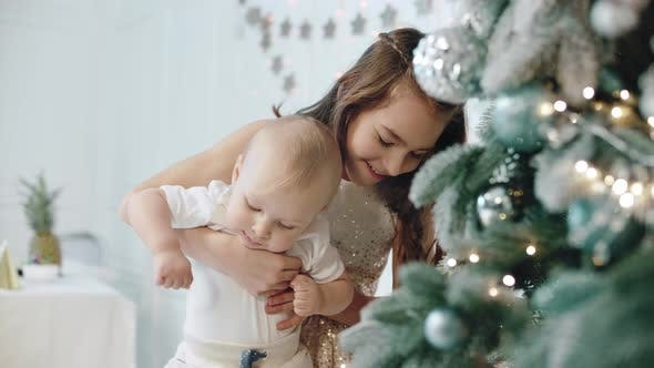Thumbnail for Closeup Happy Girl Holding Kid Near Christmas Tree in Modern House.