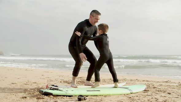 Father and Son with Surfboards on Beach