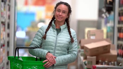 Portrait of a Beautiful Smiling Adult Woman with a Grocery Basket in Her Hands in the Supermarket