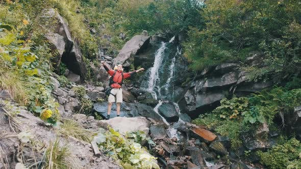 Thumbnail for Tourist with Backpack Came To Mountain Waterfall and Spreading Arms To Sides