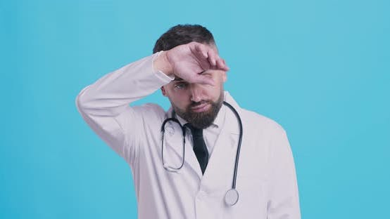 Thumbnail for Studio Portrait of Tired Medical Doctor, Wiping Off Sweating Forehead