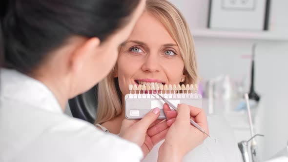 Thumbnail for Close up Of Dentist Choosing Color Teeth from Palette