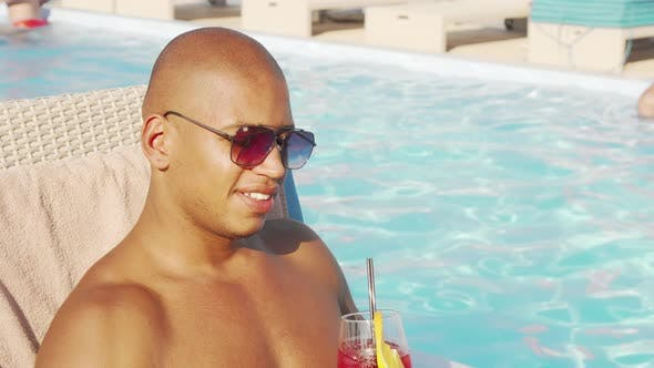 Thumbnail for Relaxed Handsome African Man Sipping His Cocktail By the Swimming Pool