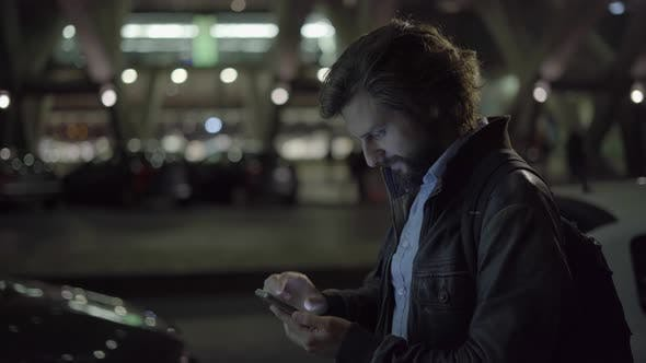 Thumbnail for Happy Young Man Chatting on Smartphone at Night