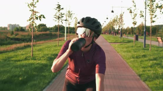 Thumbnail for Portrait of young female athlete is pedaling on bicycle on cycle path at sunset drinking water