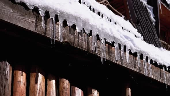 Thumbnail for Icicles Melt and Dripping on the Sun Hanging on the Roof of Wooden House. Slow Motion