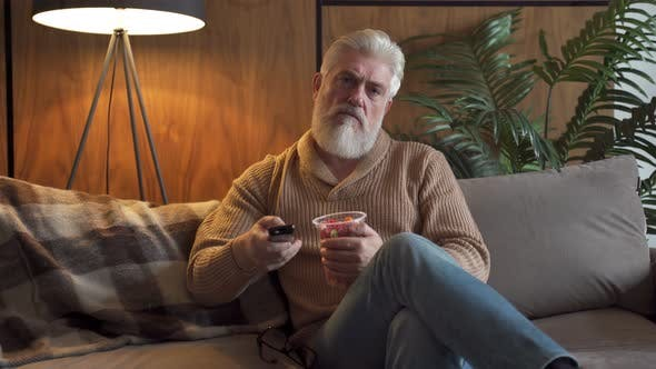 An Elderly Man with a Gray Beard Sitting on the Sofa Switches Channels on the TV Remote Control and