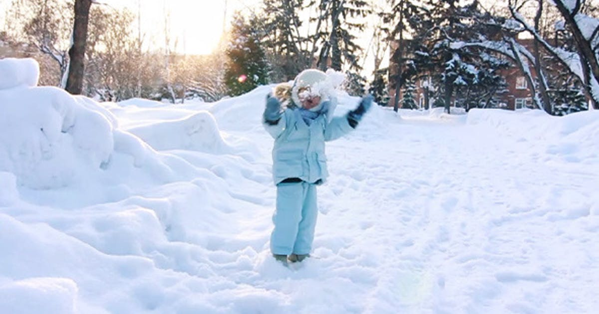 Child Playing With Snow In Park