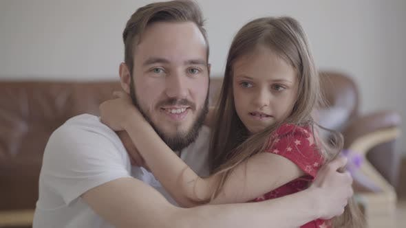 Thumbnail for The Handsome Bearded Man and Cute Positive Girl Looking in the Camera Smiling, the Child Hugging the