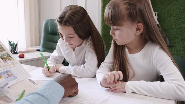 African American Teacher Teaching English Two Primary School Girls