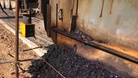 Asphalt paver lays asphalt mix on concrete base. Black top paver. Pave train