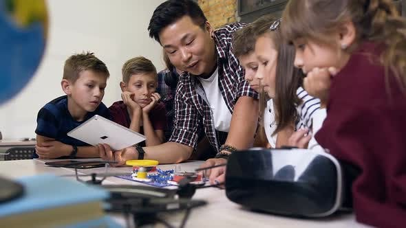 Thumbnail for Schoolchildren with Teacher Using Digital Tablet when Launching Fan in an Electronic Constructor