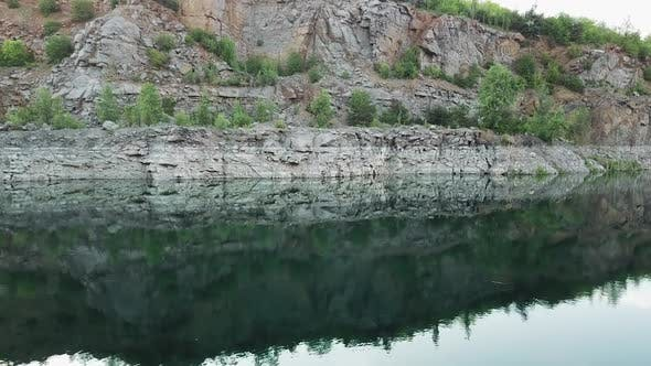 4K aerial video. Smooth takeoff above the water surface. Abandoned quarry