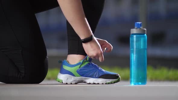 Cover Image for Sneaker of Fat Woman Jogger During Tying Shoelaces