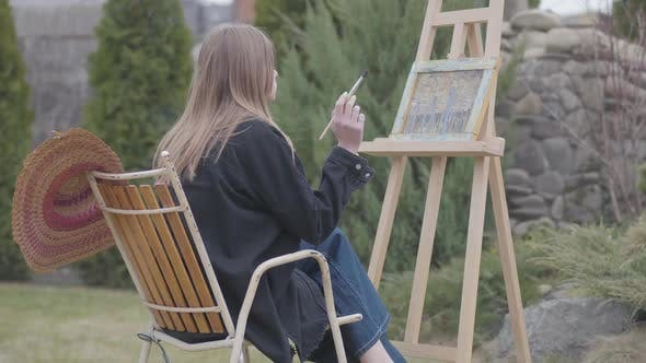 Thumbnail for Back View Portrait of the Young Girl Painter Sitting in Front of Wooden Easel Drawing a Picture and