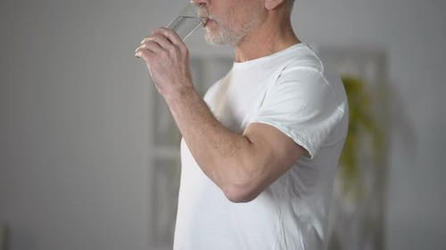 Senior Man Drinking Purified Water From Glass, Restoring Ph Balance, Healthcare