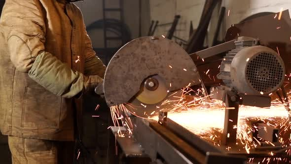 Worker Cuts Metal Rods with Grinder