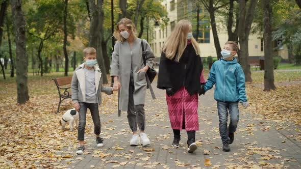 Thumbnail for Wide Shot Portrait of Young Beautiful Caucasian Women in Covid Face Masks Walking Along the Alley in