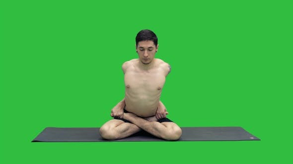 Sporty beautiful young man practicing yoga sitting cross-legged