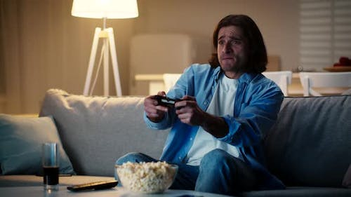 Millennial Guy Playing Video Game with Joystick and Losing Feeling Despair and Disappointment at