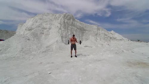 Sporty man lifting heavy barbell in the mountains. Bodybuilder doing his workout