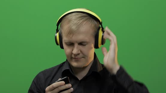 Thumbnail for Guy Listens To Music in Wireless Yellow Headphones and Dances. Green Screen