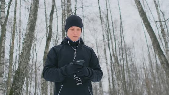 Thumbnail for A Young Man in a Black Trigger in the Winter Is Preparing To Jog in the Park Includes Running Music