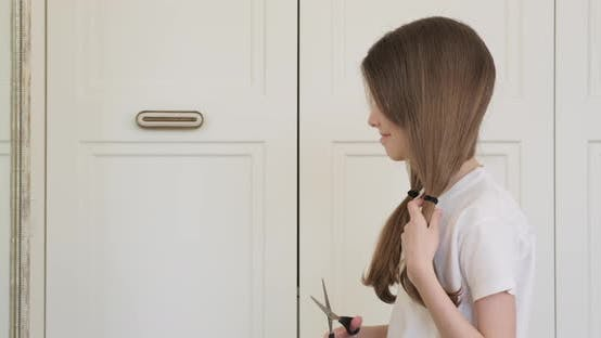 Thumbnail for Funny Girl Child Cutting Her Hair with Scissors Sitting at Home in Front of a Mirror. Beauty