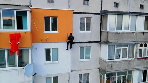 Painting and Decorating Buildings. Worker on a Construction Site of a High-rise Building. Dangerous