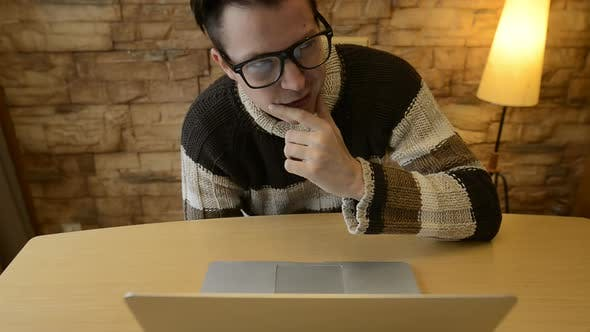 Thumbnail for Happy Young Man Thinking and Imagining While Using Laptop at Home