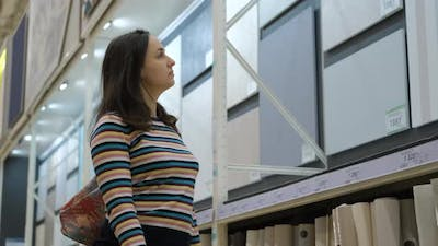 Young Woman Selects Wallpapers for Her Home