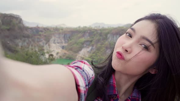 Asian backpacker woman record vlog video on top of mountain, using mobile phone make vlog video.