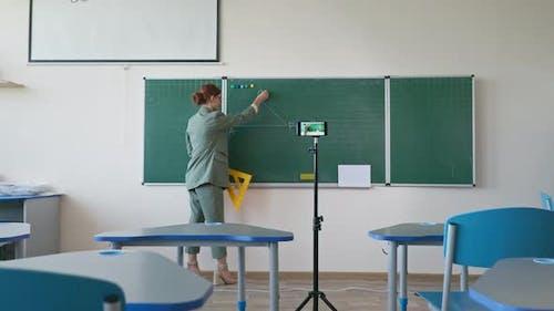 Online-Bildung Pädagoge in Brille mit Lineal in der Nähe von Tafel mit Handy-Kamera-Aufnahme