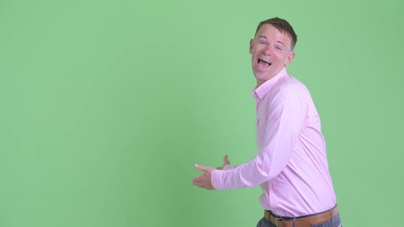 Cover Image for Portrait of Happy Businessman Showing To Back and Looking Surprised