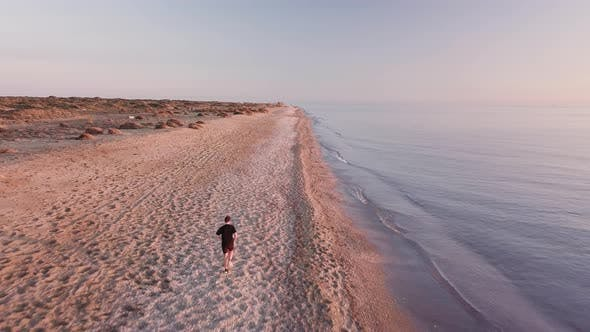 Thumbnail for Young runner man training on beautiful sunset at beach