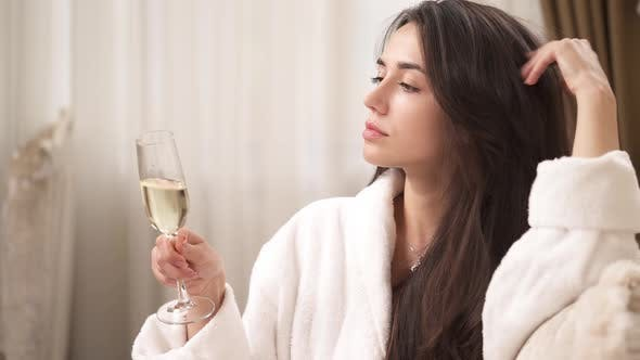 Thumbnail for A Side View of a Charming Brunette in a White Gown Sitting in the Room