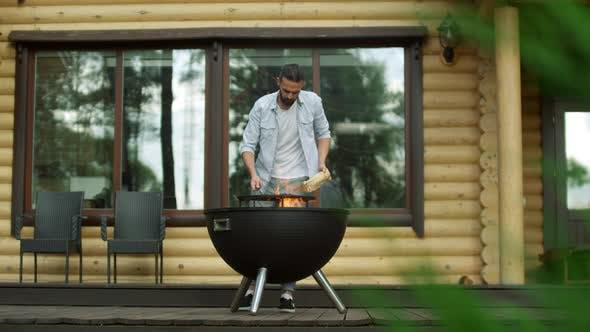 Thoughtful Man Putting Firewood in Bbq Grill