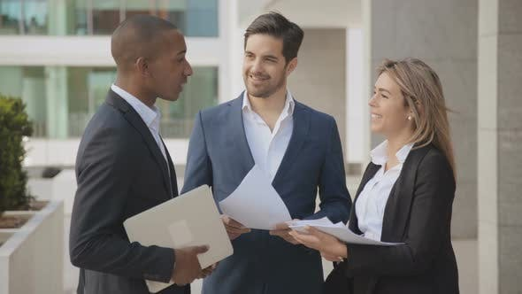 Thumbnail for Smiling Business Colleagues Discussing Work Outdoor