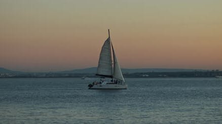 Sunset view of a lonely boat sailing in the ocean, with a city harbor in the background