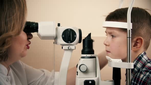 Thumbnail for Boy Having a Treatment in Eye Clinic - a Woman Doctor Checking Little Boy's Eye Vision By Looking