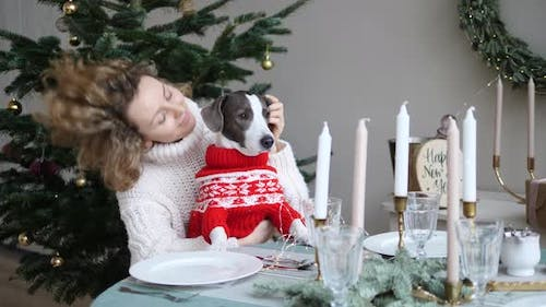 Lovely Dog and Owner Company in Cosy Sweaters Sitting at Festive Table with Candles Next to