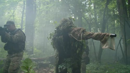 Counterterrorist Special Forces Group Wading Thicket of Forest in Fog