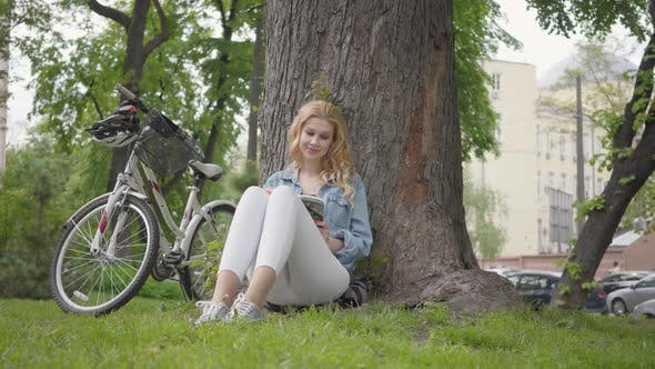 Cover Image for Pretty Smiling Woman Sitting Under an Old Tree in the Park Reading a Journal. The Modern Bicycle
