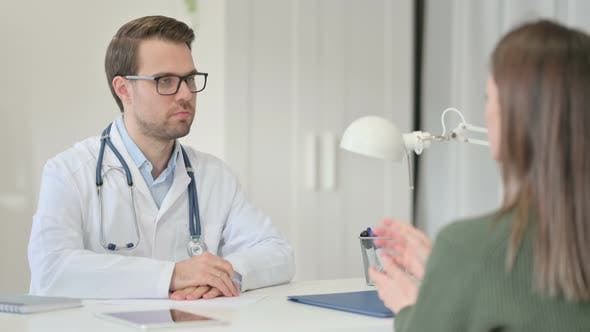 Male Doctor Discussing Medical File with Patient