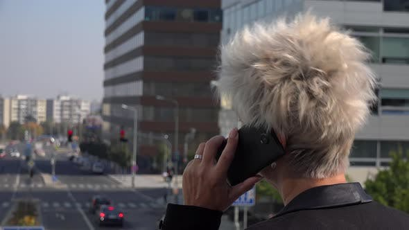 Thumbnail for A Middle-aged Woman Stands on a Bridge in an Urban Area and Talks on a Smartphone - Closeup