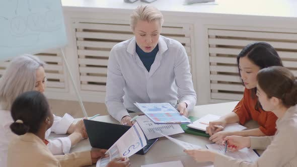 Caucasian Businesswoman Leading Meeting with Colleagues