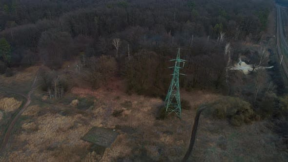 Isolated transmission tower. Green electricity pylon in forest, aerial drone shot. Power line
